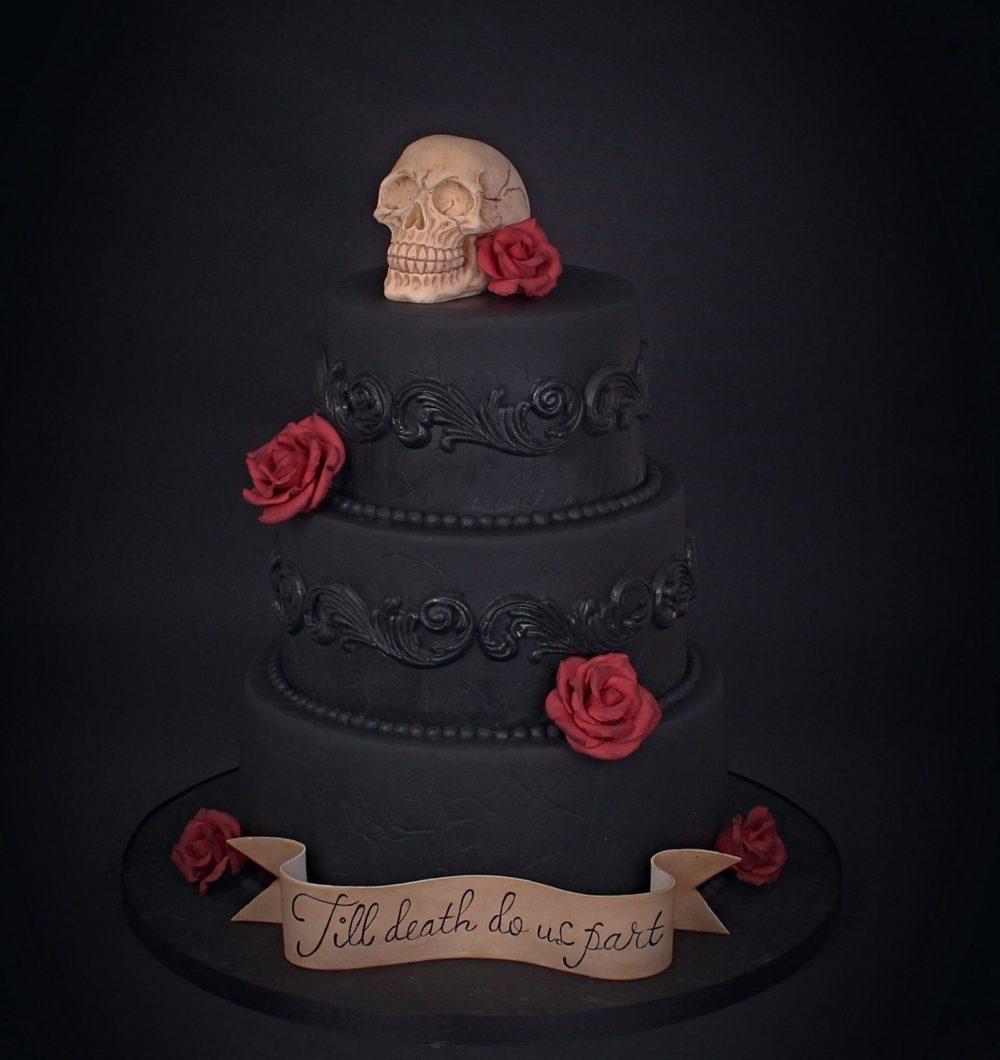 Musta hääkakku Gothic teemalla. Suklainen pääkallo kakun päällä.