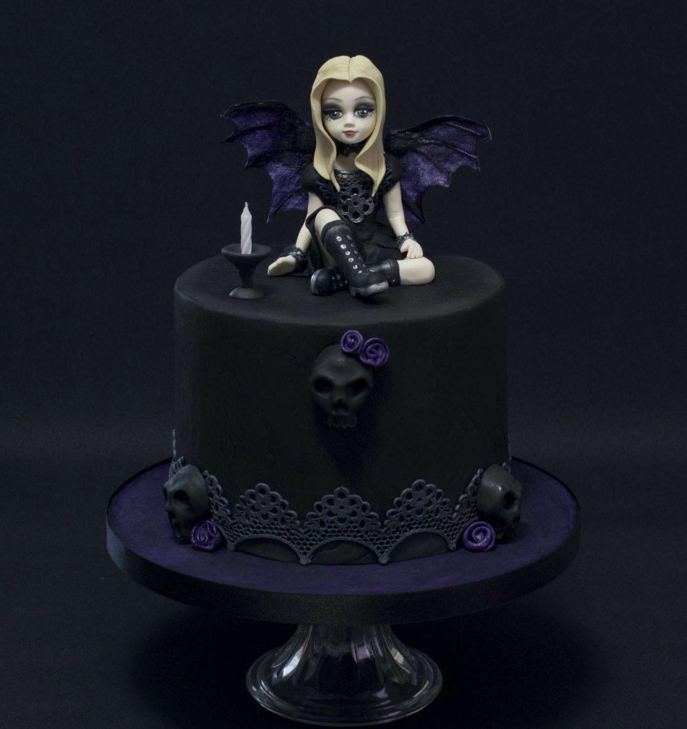 Musta violetti Gothic kakku jossa tyttö istuu kakun päällä siivet selässä.