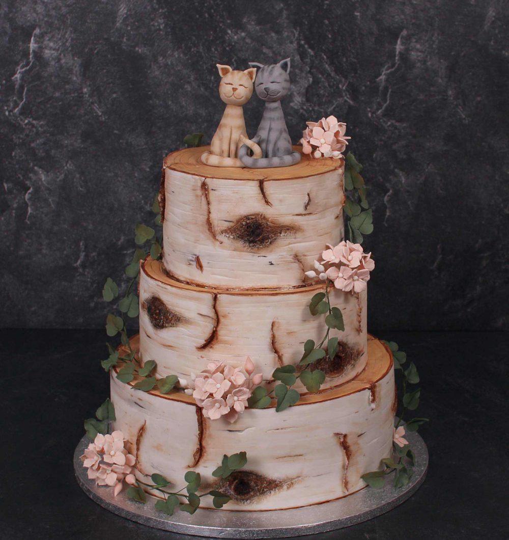100 hengen hääkakku koivupölliteemalla jossa kukat kiertää kakkua ja kissat istuvat kakun päällä.